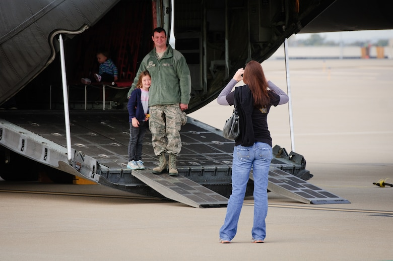 Amanda Fazio takes a photo of her daughter, Ava, and husband, Staff Sgt. Chad Fazio, an electrician with the Kentucky Air Guard's 123rd Civil Engineer Squadron, as they tour a C-130 aircraft on the flight line of the Air Guard Base in Louisville, Ky., on Oct. 23, 2011. The display was part of Family Day activities that drew more than 1,000 to the 123rd Airlift Wing. (U.S. Air Force photo by Senior Airman Maxwell Rechel)