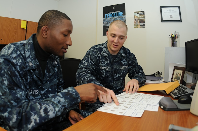 Petty Officer 3rd Class Ryan Davis (left) and Petty Officer 2nd Class Eric Martin review the Standard Form 87 fingerprint card and other important paperwork to ensure their accuracy prior to the forms being mailed to the Electronic Questionnaire for Investigation Processing department at  the Office of Personnel Management in Boyers, Pa. Martin is a Machinist's Mate assigned to the 628th Security Forces Squadron Information Protection office at Joint Base Charleston – Weapons Station and Davis is a Ship's Serviceman assigned to Naval Support Activity's Unaccompanied Personnel Housing office at JB Charleston-Weapons Station. (U.S. Navy photo/Petty Officer 1st Class Jennifer Hudson)