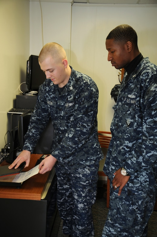 Petty Officer 3rd Class Ryan Davis watches as Petty Officer 2nd Class Eric Martin places the Standard Form 87 fingerprint card into an Identaprint machine which heats the paper and red ink, allowing the finished result to appear black in color. Martin is a Machinist's Mate assigned to the 628th Security Forces Squadron Information Protection Office at Joint Base Charleston – Weapons Station and Davis is a Ship's Serviceman assigned to Naval Support Activity's Unaccompanied Personnel Housing office at JB Charleston-Weapons Station. (U.S. Navy photo/Petty Officer 1st Class Jennifer Hudson)