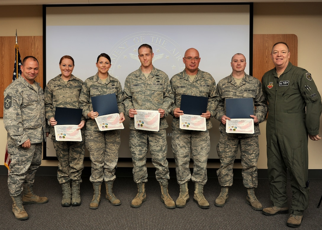 New York Air National Guard Col. Kevin Bradley (right), 174th Fighter Wing Commander, and Chief Master Sgt. Russell Youngs (left), 174th FW Command Chief, present Airmen of the Year awards to Hancock Field ANG Base personnel (from left to right) Senior Airman Cherice Baldwin, Senior Airman LeAnne Stevens, Master Sgt. Daniel Lasky, Master Sgt. Richard Macumber, and Staff Sgt. Edward Scalise on 7 January 2012.  The awards represented outstanding performance at the levels of Airman, NCO, Senior NCO, First Sergeant, and Honor Guard categories. (U.S. Air Force photo by Tech Sgt. Ricky Best/RELEASED)