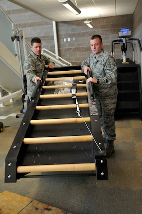 Tech. Sgt. Robert McFadden, 151st Air Refueling Wing, and Staff Sgt. Seth Mayer, Utah Air National Guard recruiter, help set up a Jacobs Ladder in the base gym at the Utah ANG base in Salt Lake City, Utah, Jan. 11, 2012. McFadden and Mayer are part of a team in charge of moving the gym equipment from the old base gym to the new location in the new fire station building on the base.  (U.S. Air Force Photo by Tech. Sgt. Jeremy Giacoletto-Stegall/Released)