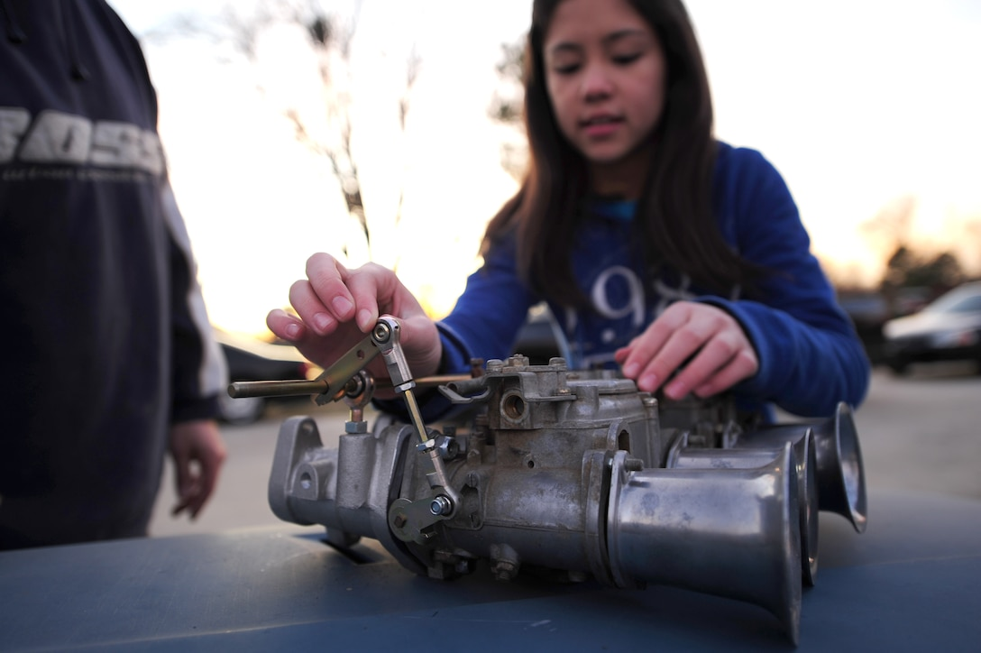 Alicia Stanton, 12, attaches a throttle linkage to a carburetor at her home in Goldsboro, N.C., Jan. 5, 2012. Since she was three years old Alicia has worked with her father, Master Sgt. Marty Stanton, 4th Logistics Readiness Squadron vehicle management superintendent, to fix and repair vehicles. (U.S. Air Force photo by Senior Airman Rae Perry)