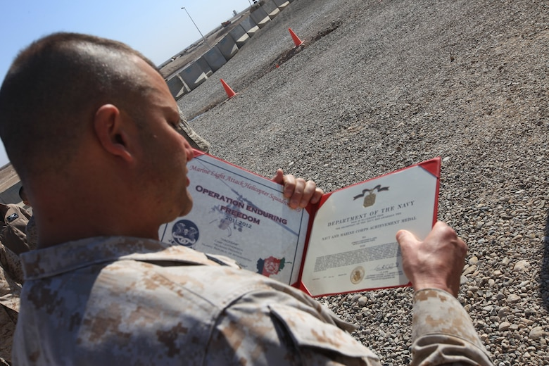 Sgt. Maj. Michael E. Golden, sergeant major of Marine Light Attack Helicopter Squadron 369, reads the award citation for Sgt. Christopher at Camp Bastion, Afghanistan, Jan. 12. Lemke, a mechanic with the squadron, and a native of Macomb, Mich., discovered a previously unknown issue with the UH-1Y Huey helicopter that represented an extreme risk to the aircraft and aircrew. The Marine was awarded the Navy and Marine Corps Achievement Medal for his potentially lifesaving find.