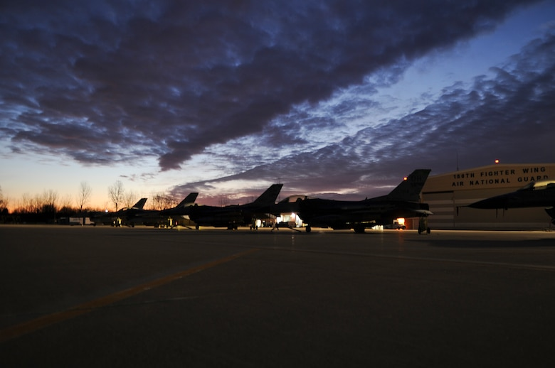 F-16CG aircraft silhouette the flightline in the early morning hours at the 180th Fighter Wing, Ohio Air National Guard, Swanton, Ohio. The 180th Fighter Wing performed a unit training assembly Jan. 7 and 8, 2012 where traditional status guardsmen participate in once monthly training activities such as flying and maintaining these aircraft.(U.S. Air Force photo by Master Sgt. Beth Holliker/Released)