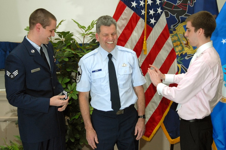 Senior Master Sgt. Stephen Agnew is promoted to chief master sergeant during a ceremony held here Mar. 5, 2011. Tacking his news stripes on are his sons Senior Airman Stephen Agnew, Jr. and Jason Agnew.