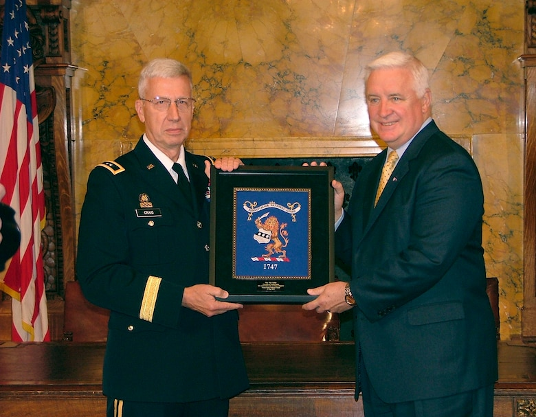 Army Maj. Gen. Wesley Craig, Adjutant General of the Pennsylvania National Guard, presents Pennsylvania Governor Thomas Corbett (R) with an embroidered plaque, featuring the Pa. National Guard emblem, on Flag Day, June 14, 2011 at a ceremony held during 'Guard Day at the Capitol' in Harrisburg, Pa. The date presented approximates what would have been Corbett's 40th anniversary of his enlistment with the Guard.