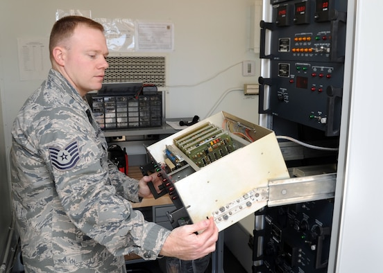 ALTUS AIR FORCE BASE, Okla. – Tech. Sgt. Brandon Sutliff, 97th Communications Squadron, NCO in charge of airfield systems, opens the inside of an instrument landing system at the 35 right airfield, Jan. 13, 2011. An ILS transmits, monitors and distributes frequencies to antennas on the airfield that travels to the aircraft, helping pilots land during inclement weather. (U.S. Air Force photo by Airman 1st Class Franklin Ramos / 97th Air Mobility Wing Public Affairs / Released)