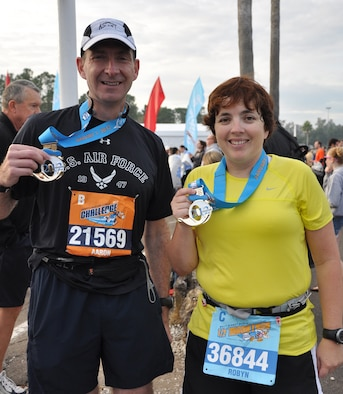 Col. Aaron Prupas (left), commander of the Air Force Technical Applications Center at Patrick Air Force Base, Fla., and Robyn Kleinschmidt, wife of Maj. Neal Kleinschmidt, also from AFTAC, display their coveted Donald Duck medals upon completion of Disney's half marathon that took place Jan. 7, 2012.   Runners journeyed through various locations throughout Walt Disney World during the 13.1-mile trek.  (U.S. Air Force photo/Susan A. Romano)
