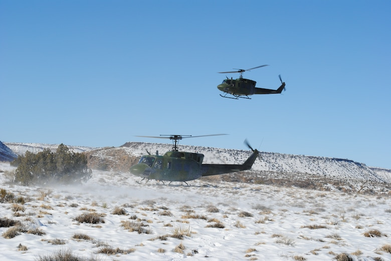 A UH-1N assigned to the 512th Rescue Squadron lands while another hovers overhead Dec. 27. U.S. Air Force Photo by John Cochran.