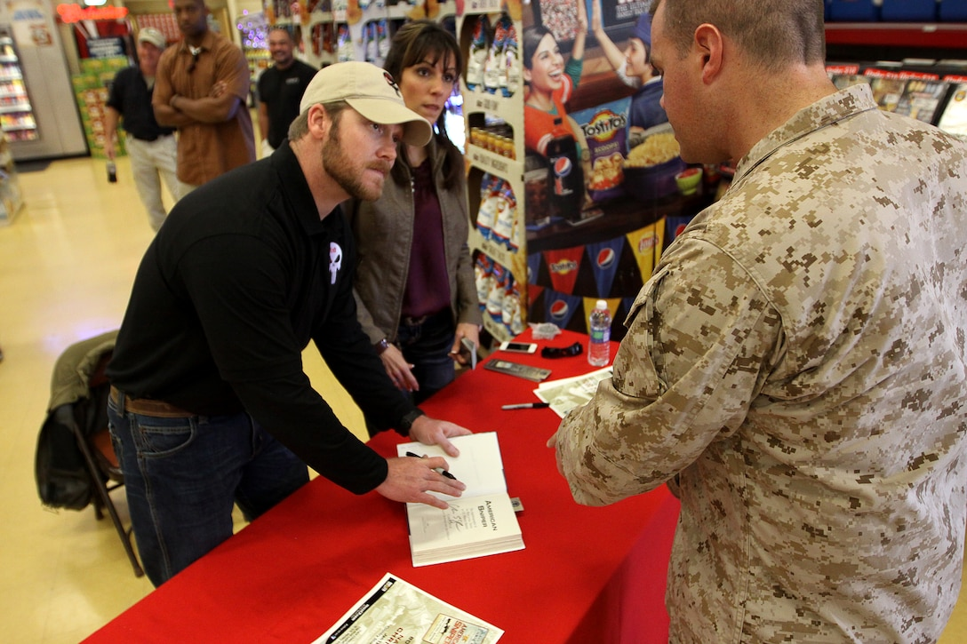 """Navy Seal Sniper Chris Kyle signs a copy of his new book """"American Sniper"""" for a Camp Pendleton sailor at the base's Country Store, Jan. 13. """"American Sniper"""" is Kyle's first person account of how he went from a Texas cowboy to one of the most distinguished snipers in the military. The book also offers a view of modern warfare and one of the most in-depth looks into the secret world of special operations."""