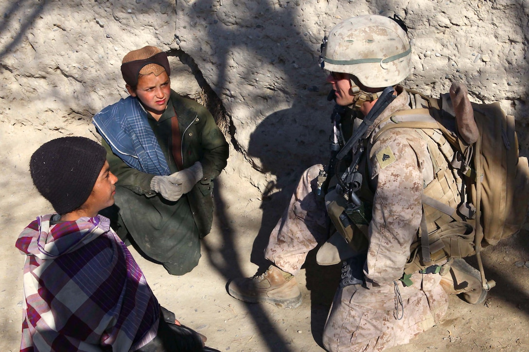 A Marine with I Co., 3rd Battalion, 7th Marine Regiment, talks with children from a small village near Sangin, Afghanistan, during a routine security Patrol. The Marines of I Co. maintain a good relationship with the local villagers by conducting security patrols along with members of the Afghan National Army.