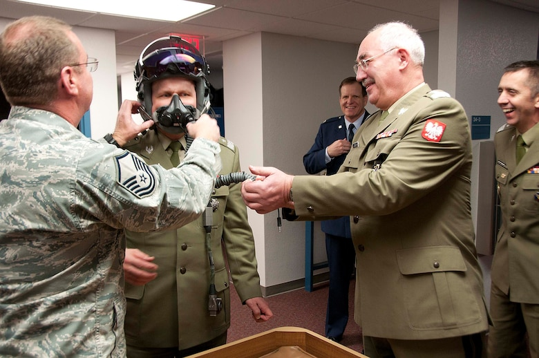 Polish Army Maj. Gen. Andrzej Falkowski, the Polish Defense Attaché to Washington D.C., tries on an F-16 pilot's helmet equipped with the joint helmet-mounted cueing system with help from Master Sgt. Don Lauver while Polish Army Gen. Mieczyslaw Cieniuch (right), Chief of the General Staff of the Polish Armed Forces, observes Jan. 12. (U.S. Air Force photo/Master Sgt. Dave Neve)