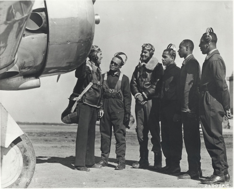 Members of the first pilot class at the advanced flying school at Tuskegee, Alabama, listening to their instructor, 1942.