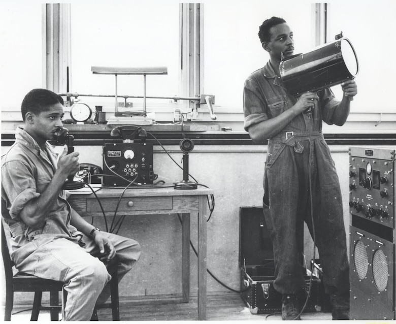 Support staff training in control tower with microphone and biscuit gun, 1942.