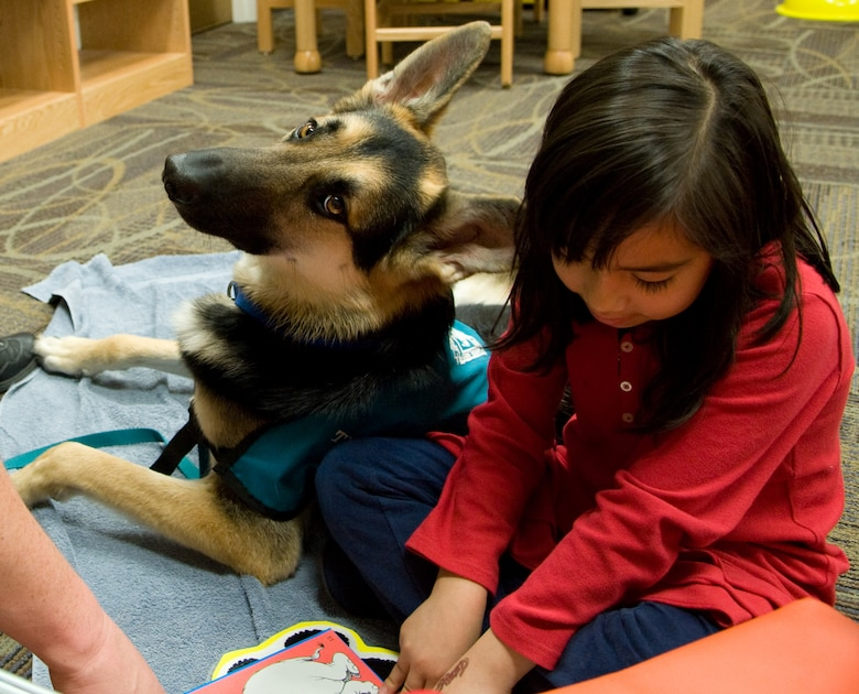 Barb Brewer, a volunteer for the Paws for Reading Program, and her dog, Toby, help Sandra Mendoza learn a new word during her reading session at the Mitchell Memorial Library, Jan. 12. The Paws for Reading program helps kids gain confidence in their reading skills. (U.S. Air Force photo/ Airman 1st Class Nicole Leidholm)