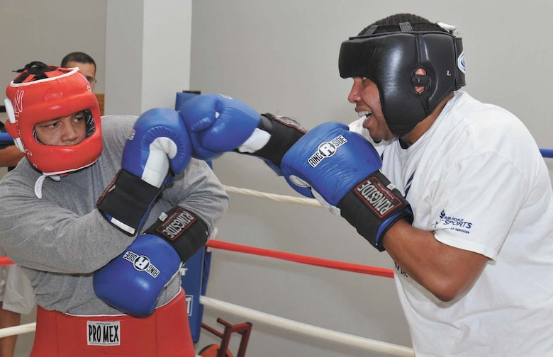 Air Force boxer Kent Brinson fends off a right jab from opponent Forrest Booker during a sparring session at the Chaparral Fitness Center. (U.S. Air Force photo/Alan Boedeker)