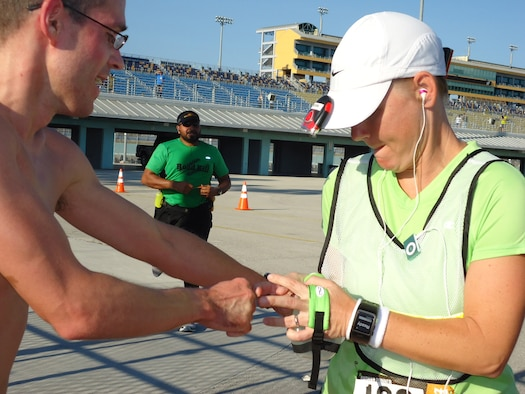 Myron Larrick, left, a member of the Air Force Technical Applications Center at Patrick AFB, Fla., passes the baton – or in this case, a slap bracelet – to fellow Ragnar Relay Race teammate Erica Reich at Homestead International Raceway Jan. 7, 2012. Larrick had just completed a 9-mile leg with his final lap around the speedway, while Reich was about to begin her 6-mile leg toward the Florida Everglades. The nationally-acclaimed, 198.5-mile race tests the physical and mental limits of its participants. (Courtesy photo)