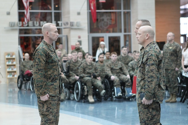 Wounded, ill and injured Marines with the U.S. Marine Corps Wounded Warrior Regiment look on as Sgt. Maj. John Ploskonka stands at attention in front of Col. John Mayer, Wounded Warrior Regiment commanding officer and Sgt. Maj. Joseph E. VanFonda during a post and appointment ceremony Jan. 23, at the National Museum of the Marine Corps here.  During the ceremony Sgt. Maj. Ploskonka passed his duties as regimental sergeant major of the Wounded Warrior Regiment to Sgt. Maj. VanFonda.  Ploskonka was selected to serve as the sergeant major of the Marine Corps Installations Command, Arlington, Va.
