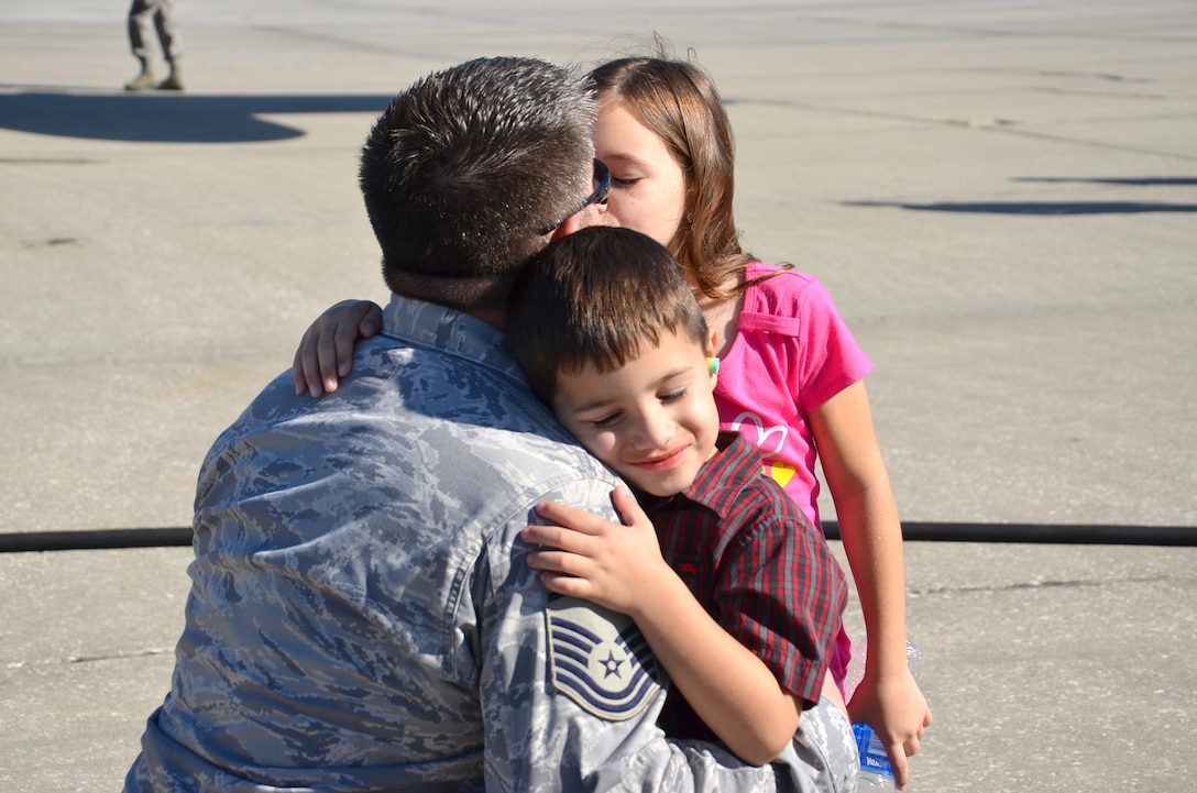 Master Sgt. Joel Lindsey, electronic integrated systems supervisor, 920th Rescue Wing, Patrick Air Force Base, Fla., gives his daughter and son a hug and kiss Jan 25. Lindsey is one of approximately 60 Rescue Airmen deploying to the Horn of Africa for 120 days to support the ongoing search and rescue and humanitarian relief efforts there. (U.S. Air Force photo/Senior Airmen Natasha Dowridge)