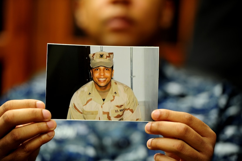 Petty Officer 1st Class Frank Newsom holds up a photo of himself when he was on his first Individual Augmentee deployment, Jan. 19 at Joint Base Charleston - Weapons Station. There were more than 8,000 Navy IA deployments last year taking Sailors to 14 different locations from Central America to the Middle East to serve in an array of different combat support roles. Newsom is preparing for another one-year IA to Afghanistan where he will provide protective services for a senior officer. Newsom is a Master-at-Arms at the 628th Security Forces Squadron.  (U.S. Air Force photo/ Staff Sgt. Nicole Mickle)