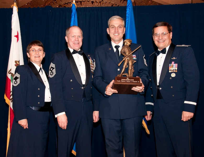 Master Sergeant Peter Kelley (center) from the 163rd Reconnaissance Wing  accepts the Outstanding Airman of the Year award in the Senior NCO category. Accompanied by Chief Master Sgt. Debra Fordyce, (far left) Command Chief Master Sgt. Christopher Muncy, (left) and Brigadier General James Witham at the annual Outstanding Airman Of The Year Awards Banquet at The Sheraton Universal Hotel, Universal City, Calif., January 21, 2012. Each organization nominated four candidates for Airman of The Year, NCO of The Year, Sr. NCO of The Year and First Sergeant of The Year. U.S. Air Force photo by Tech. Sgt. Alex Koenig