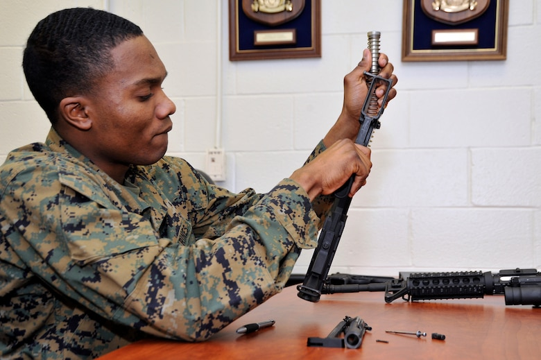 Marine Lance Cpl. Jean Baptiste Henry, Marine Transport Squadron operations technician, field strips an M4 rifle during his Lance Corporal's Course here, Jan. 10. The course provides training in drill, Marine Corps history, codes of conduct, mentorship and many other classes geared toward improving the Marines before they take on the responsibility of becoming NCOs. (U.S. Air Force Photo/Senior Airman Perry Aston)