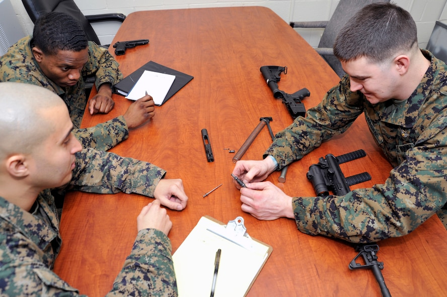 Marine Sergeant Daniel Bason, Marine Transport Squadron Andrews operations chief, refreshes Lance Corporals Samael J. FanesteEspina and Jean Baptiste Henry, Marine Transport Squadron Andrews operations technicians, on how to field strip the M4 carbine rifle during their Lance Corporal's Course here, Jan. 10. The course provides training in drill, Marine Corps history, codes of conduct, mentorship and many other classes geared toward improving the Marines before they take on the responsibility of becoming NCOs. (U.S. Air Force Photo/Senior Airman Perry Aston)