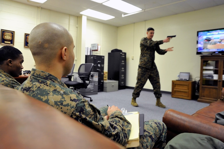 Marine Sergeant Daniel Bason, Marine Transport Squadron Andrews operations chief, teaches Lance Corporals Samael J. FanesteEspina, and Jean Baptiste Henry, Marine Transport Squadron Andrews operations technicians, Beretta M9 firing positions during their Lance Corporal's Course here, Jan. 10. The Marines, along with the rest of the services, recently replaced their use of the .45 pistol with the Beretta M9. (U.S. Air Force Photo/Senior Airman Perry Aston)