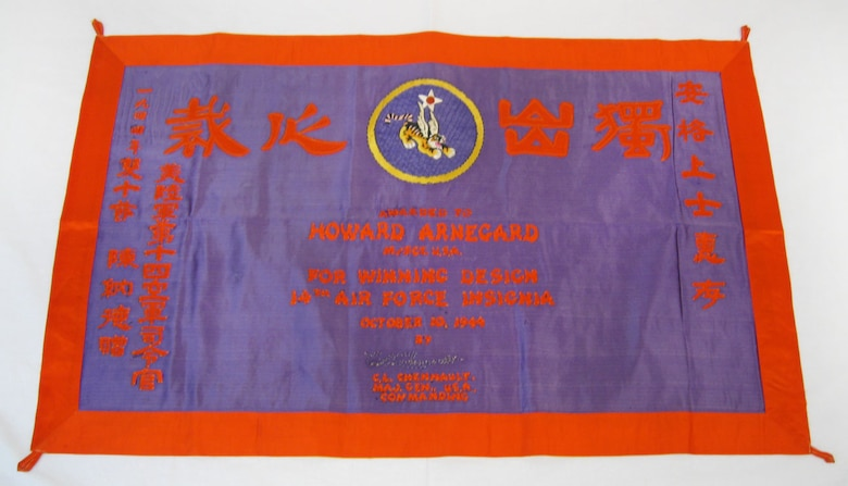 This banner was awarded to the donor's father, Howard Arnegard, for the winning design in Maj. Gen. Claire Chennault's contest for the 14th Air Force insignia. It was made in 1944 in China. The Chinese lettering translates to the English wording on the banner. (U.S. Air Force photo)