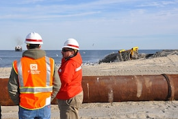Coastal Engineer Donald Cresitello and Resident Engineer Paul Jalowski, both with the U.S. Army Corps of Engineers, New York District, chat as sand is pumped into place on Monmouth Beach, N.J.
