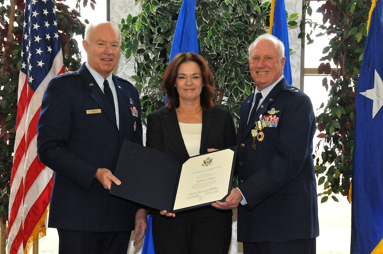 Lt. Gen. Harry M. Wyatt III (left) presents a Certificate of Appreciation to MBarbara Haynes (center) on behalf of the U.S. Air Force thanking her for her commitment and contributions during the career of her spouse, Maj. Gen. Thomas J. Haynes (right), Air National Guard Assistant to the Commander, Air Mobility Command, during Haynes' retirement ceremony at Scott Air Force Base, Ill., on Jan. 27, 2012.