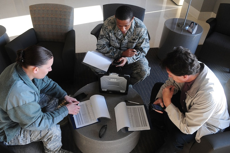 U.S. Air Force Staff Sgts. Sarah Kearney, left, Oris Key, center, both from the 633rd Security Forces Squadron, and Ken Hughes, Air Force Integrations Center systems engineer, analyze data during a Joint Expeditionary Force Experiment exercise at Langley Air Force Base, Va., Jan. 25, 2012. The month long exercise was held to assess multiple cellular solutions for enhanced speed and cost reductions. (U.S. Air Force photo by Staff Sgt. Ashley Hawkins/Released)