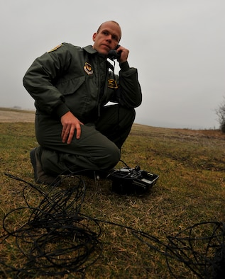 BAUMHOLDER, Germany – U.S. Air Force 1st Lt. Matt Kading, 81st Fighter Squadron pilot, uses a field-operated local-area-connection phone to call the Baumholder Kommandantuer range control center during a joint forces close air support and combat search and rescue training at the Baumholder Major Training Area here Jan. 26. The training integrates U.S. Army and Air Force resources to more accurately simulate the real-life CSAR and CAS scenarios encountered in deployed locations. The goal of this training is to develop tactics, techniques and procedures between military branches to enhance interoperability. (U.S. Air Force photo/Senior Airman Natasha Stannard)