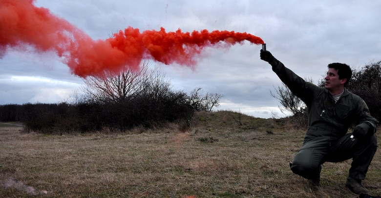 BAUMHOLDER, Germany – U.S. Air Force Capt. James Schmidt, 81st Fighter Squadron pilot, raises a signal smoke flare during joint forces close air support and combat search and rescue training at the Baumholder Major Training Area here Jan. 23 to signal a U.S. Army AH-64 Apache helicopter crew participating in the training. The training integrates Army and Air Force resources to more accurately simulate the real-life CSAR and CAS scenarios encountered in deployed locations. The goal of this training is to develop tactics, techniques and procedures between military branches to enhance interoperability. (U.S. Air Force photo/Senior Airman Natasha Stannard)