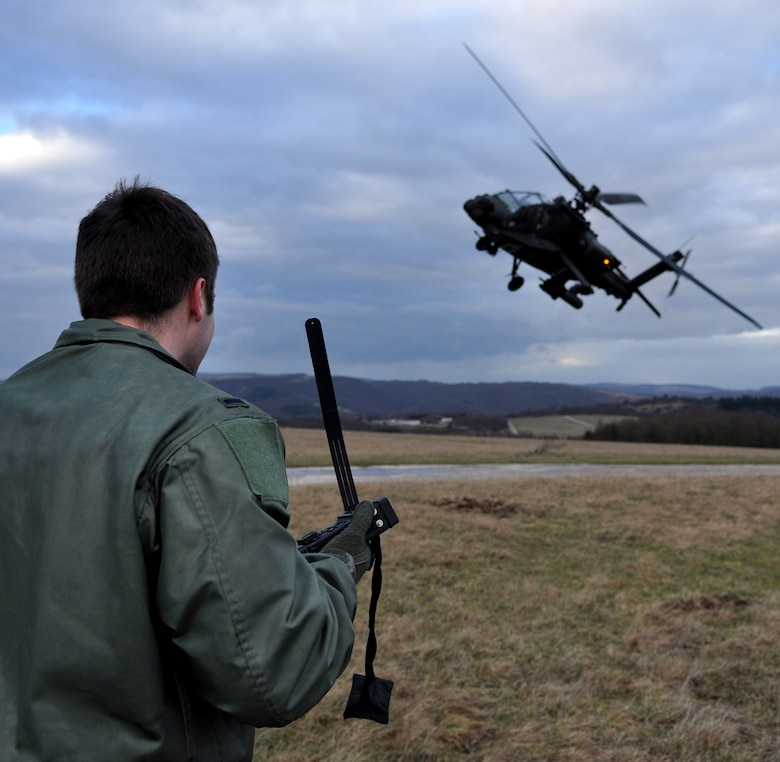 BAUMHOLDER, Germany – U.S. Air Force 1st Lt. Bob Carpenter, 81st Fighter Squadron pilot, uses a combat survivor evader locater radio to communicate that a U.S. Army AH-64 Apache helicopter that has arrived to rescue him during a joint training exercise at the Baumholder Major Training Area here Jan. 23. This training integrates U.S. Army and Air Force resources to more accurately simulate the real-life close air support and combat search and rescue scenarios encountered in deployed locations. The goal of this training is to develop tactics, techniques and procedures between military branches to enhance interoperability. (U.S. Air Force photo/Senior Airman Natasha Stannard)