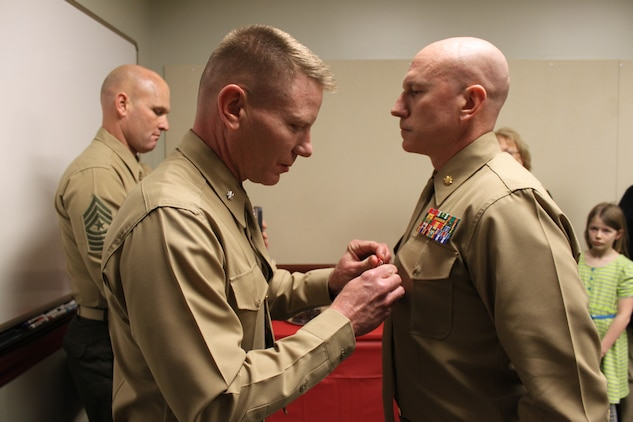 """Major Jamie P. Murphy, the Wounded Warrior Regiment's future operations officer, is presented the Bronze Star Medal with Combat """"V"""" device by Lieutenant Col. J.D. Harrill during an awards ceremony at the regimental headquarters here.  Murphy earned the Bronze Star for his heroic service in connection with combat operations against the enemy while serving in Operation Enduring Freedom.  Lieutenant Col. Harrill is the former commanding officer of 2nd Battalion, 8th Marines, Regimental Combat Team 1, 2nd Marine Division (Forward), where Murphy earned this honor."""