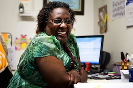 Jeannette E. Powell-Campbell, assistant adjutant, Headquarters and Service Battalion, U.S. Marine Corps Forces, Pacific, flashes that familiar smile in her office here Jan. 30. Powell-Campbell is a retired master gunnery sergeant who is the adopted mother of three Cambodian children.