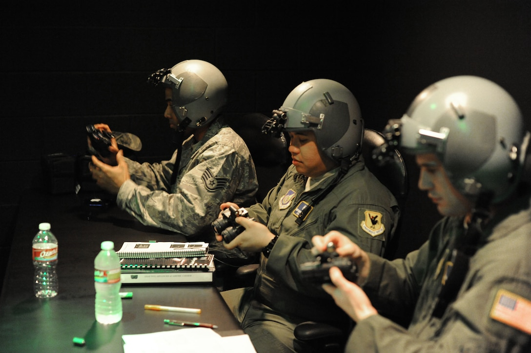 (From left) Staff Sgt. Sadek Brandford, 27th Special Operations Support Squadron aerospace physiology technician, Staff Sgt. Nazareth Oliver, 18th Aerospace Medicine Squadron and Senior Airman Clint Copeland, 18th Aerospace Medicine Squadron, learn to attach night vision goggles to their helmet during a NVG Academic Instructors Course held at the Aerospace Physiology building on Joint Base San Antonio-Randolph Jan. 25. (U.S. Air Force photo/Rich McFadden) (released)