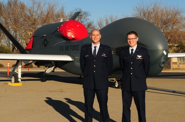 Second Lieutenants Scott (right) and Jacob (left) pose in front of an RQ-4 Global Hawk at the Beale AFB, Calif., flight line Jan. 13, 2012. Lieutenants Jacob and Scott became the first 18X pilots in the Air Force to complete RQ-4 Global Hawk training and were honored during a winging ceremony at the 1st Reconnaissance Squadron's Dively Theater. (U.S. Air Force photo by Senior Airman Shawn Nickel/Released/Portions of this photo have been masked due to operational security reasons)