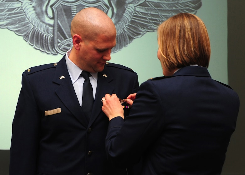 Second Lieutenant Jacob receives his remotely piloted aircraft wings from his wife, 2nd Lt. Rachael, during a winging ceremony at the 1st Reconnaissance Squadron's Dively Theater, Beale AFB, Calif., Jan. 13, 2012. 2nd Lt. Jacob, along with 2nd Lt. Scott, was one of the first two RQ-4 Global Hawk pilots to join the new 18X career field. (U.S. Air Force photo by Senior Airman Shawn Nickel/Released/Portions of this photo have been masked due to operational security reasons)