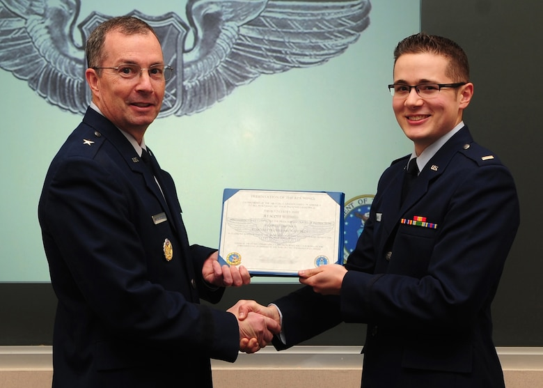 Brig. Gen. Paul McGillicuddy, 9th Reconnaissance Wing commander, presents a certificate to 2nd Lt. Scott during a winging ceremony at the 1st Reconnaissance Squadron's Dively Theater, Beale AFB, Calif., Jan. 13, 2012. 2nd Lt. Scott, along with 2nd Lt. Jacob, was one of the first two RQ-4 Global Hawk pilots to join the new 18X career field. (U.S. Air Force photo by Senior Airman Shawn Nickel/Released/Portions of this photo have been masked due to operational security reasons)