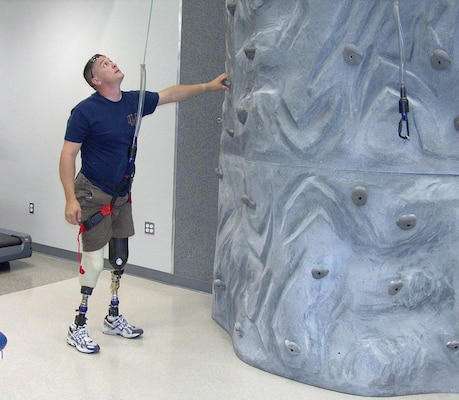 A wounded warrior uses a rock-climbing wall as part of his physical therapy at the Military Advanced Training Center at Walter Reed Army Medical Center.  Soldiers in Warrior in Transition units at Forts Stewart, Benning, Gordon and Bragg now have the option to learn valuable construction and engineering skills as part of Operation Warfighter.