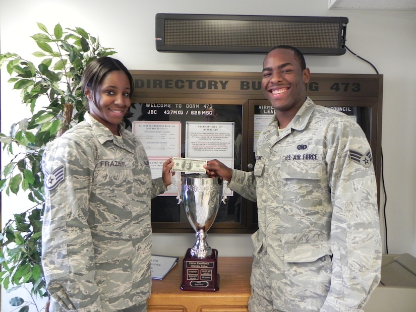 Senior Airman Cory McClure (right) accepts a crisp $100 bill on behalf of Dorm 473, from Staff Sgt. Chiquita Frazier, Jan. 26 at Joint Base Charleston - Air Base. Dorm 473 won the quarterly dorm competition and the Dorm 473 advisory council plans to use the money to benefit the dorm residents. McClure is assigned to the 628th Logistics Readiness Squadron and is the Dorm 473 council president. Frazier is assigned to the 628th Civil Engineer Squadron and is the Dorm 473 Airmen Dorm leader.  (Courtesy photo)