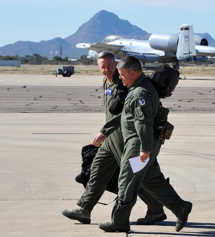 Brig. Gen. William Binger, 10th Air Force Commander, and Lt. Col. Jeffery Peterson with the Air National Guard and Air Force Reserve Test Center walk on the flight line at Davis-Monthan Air Force Base, Ariz. prior to the general's familiarization flight in an HH-60 Pave Hawk helicopter. General Binger visited the 943rd Rescue Group to visit with Airmen and learn about the group's combat-search-and-rescue capabilities. (U.S. Air Force Photo/ Master Sgt. Luke Johnson)