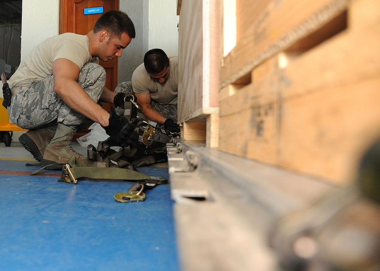 Staff Sgt. Angel Ortega (left), 571st Mobility Support Advisory Squadron air transportation air advisor, and Staff Sgt. Peter Salinas, 571st MSAS air transportation air advisor, secure cargo straps onto a pallet before loading it onto an aircraft during an Air Mobility Command Building Partner Capacity mission at General Alberto Pauwels Rodriguez Air Base in Barranquilla, Colombia, June 27.  (U.S. Air Force photo by Tech. Sgt. Lesley Waters)