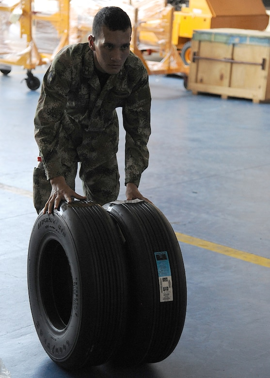 A Colombian air force member moves aircraft tires for palletizing during an Air Mobility Command Building Partner Capacity mission at General Alberto Pauwels Rodriguez Air Base in Barranquilla, Colombia, June 27.  (U.S. Air Force photo by Tech. Sgt. Lesley Waters)