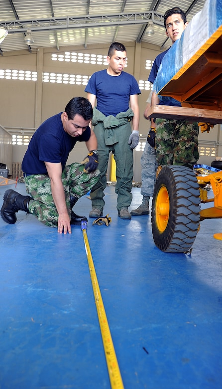 Members of the Colombian air force take measurements on a generator for loading onto aircraft during an Air Mobility Command Building Partner Capacity mission at General Alberto Pauwels Rodriguez Air Base in Barranquilla, Colombia, June 27.  (U.S. Air Force photo by Tech. Sgt. Lesley Waters)