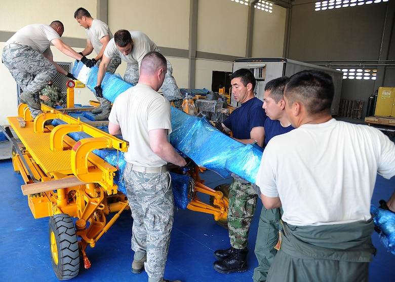 Members of the 571st Mobility Support Advisory Squadron and the Colombian air force, load gear onto rolling stock before weighing and loading it onto an aircraft during an Air Mobility Command Building Partner Capacity mission at General Alberto Pauwels Rodriguez Air Base in Barranquilla, Colombia, June 27.  (U.S. Air Force photo by Tech. Sgt. Lesley Waters)