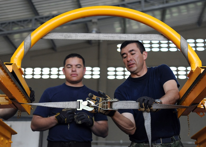 Members of the Colombian air force use a cargo strap to secure loose equipment before loading it onto an aircraft during an Air Mobility Command Building Partner Capacity mission at General Alberto Pauwels Rodriguez Air Base in Barranquilla, Colombia, June 27.  (U.S. Air Force photo by Tech. Sgt. Lesley Waters)