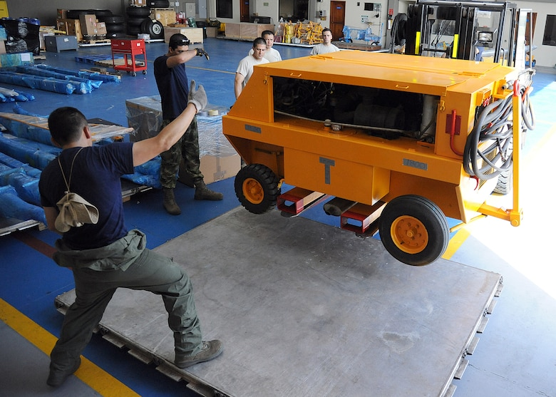 Members of the 571st Mobility Support Advisory Squadron and the Colombian air force, position a generator onto a pallet before loading it onto an aircraft during an Air Mobility Command Building Partner Capacity mission at General Alberto Pauwels Rodriguez Air Base in Barranquilla, Colombia, June 27.  (U.S. Air Force photo by Tech. Sgt. Lesley Waters)